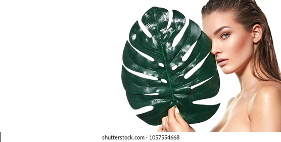A beautiful young girl in the studio on a white background with wet skin and wet hair holds a large green tropical leaf in hands and covers a part of her face.fashion, beauty, makeup, cosmetics.