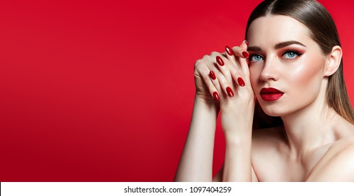 Beautiful young girl in studio on gray background. Close-up portrait. Hairstyle styling. Smooth shiny hair and skin. Red lips, red nails.