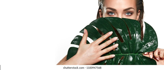A beautiful young girl in the studio on a white background with wet skin and wet hair holds a large green tropical leaf in hands and covers a part of her face.