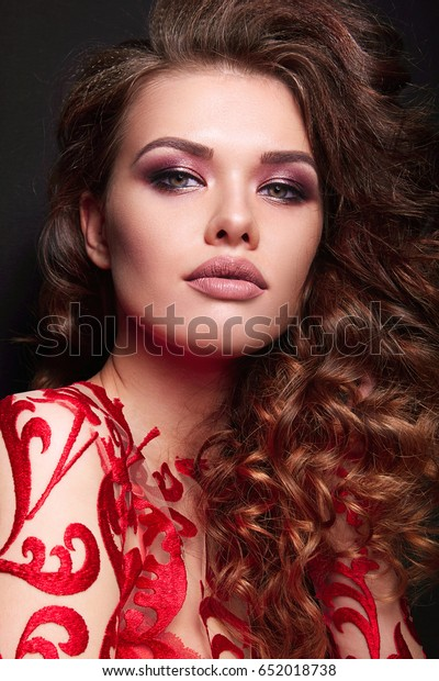 Beautiful young girl in studio on dark background in profile. Lush hair - small curls, curls, brown-haired. Clothes - a red dress. Close-up. Cosmetics. Makeup - shades of metallic, beige lipstick.