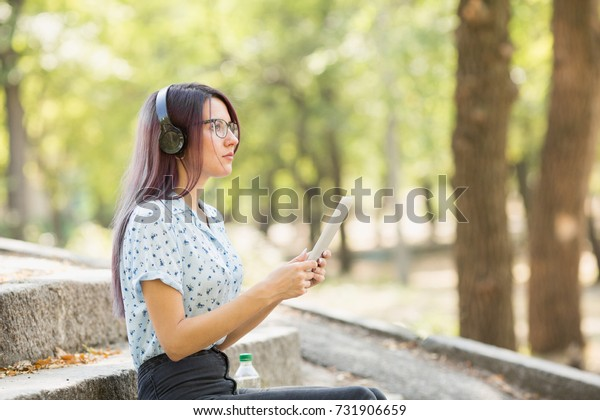 Beautiful young girl studying on a tablet on a park background. Self-education concept. Copy space.