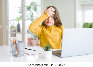 Beautiful young girl studying for school using computer laptop stressed with hand on head, shocked with shame and surprise face, angry and frustrated. Fear and upset for mistake.