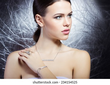 beautiful young girl with beautiful stylish expensive jewelry, necklace, earrings, bracelet, ring, filming in the Studio