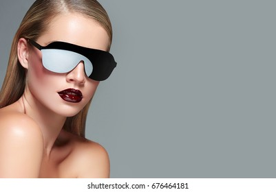Beautiful young girl in sunglasses with mirror glasses in the studio. Fashion, beauty, beach, sun.Fashionable accessories.