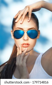 Beautiful young girl in sunglasses on blue background