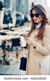 Beautiful and young girl in sunglasses writes a message on a cell phone and drinking coffee outdoors