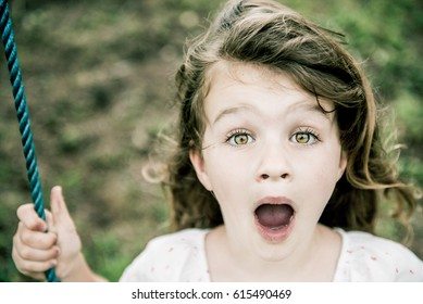 beautiful young girl with surprised look on her face on a swing