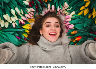 beautiful young girl taking selfie in bunch of tulip flowers