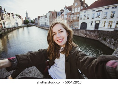 Beautiful young girl taking selfie self-portrait near canals in Bruges, Belgium. Pretty student takes funny portrait for travel blog.