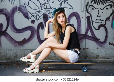 Beautiful young girl, with tattoo on her arm, wearing in cap, sandals, shirt and shorts, posing on her skateboard, near the wall with graffiti, in the park, full body
