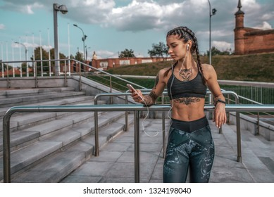 Beautiful young girl tattoos, summer city, hand smartphone listens music headphones, sportswear, leggings bra. Free space for text. Online on Internet social networks. In morning fitness open air.