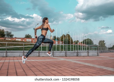 Beautiful young girl tattoos, summer city, runs jump , in hand smartphone listens music in headphones sportswear leggings bra. Free space text. Morning exercise in fresh air on background blue sky.
