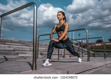 Beautiful young girl in tattoos summer city, stretching muscles of legs before training sportswear leggings and bra. In morning before jogging and fitness in open air. Concept of healthy lifestyle.