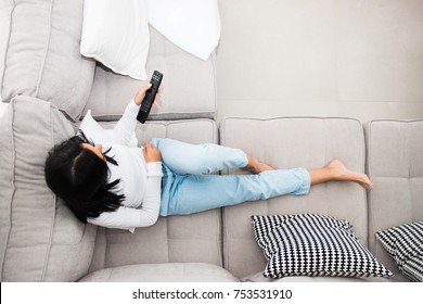 Beautiful young girl with a television remote