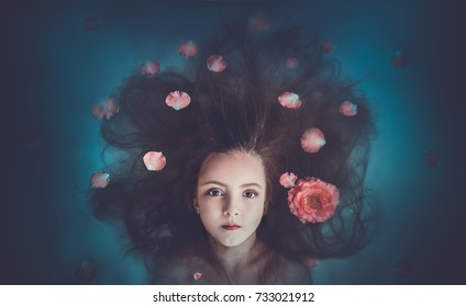 Beautiful young girl with thick long hair peeps out of the water with flower petals floats in the water, a mermaid fairy-tale concept of beauty spa relaxation chic prestigious luxury rest cometology