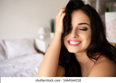 beautiful young girl touching hair and smiling with closed eyes