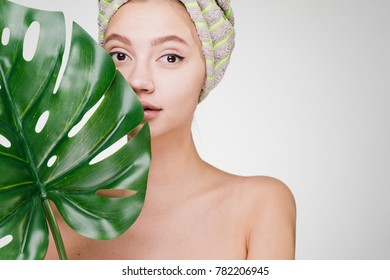 beautiful young girl with a towel on her head holds in her hand a big green leaf, a spa day