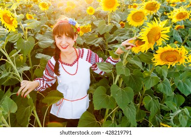 Beautiful young girl in traditional ukrainian blouse embrodery looking to camera on a sunflower plant at sunset, backlight.