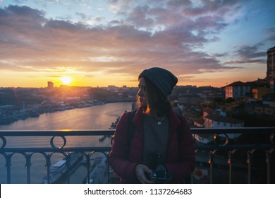 Beautiful young girl traveler standing at sunset overlooking the city of Porto, Portugal, in the rays of the setting sun