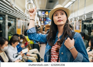 beautiful young girl traveler taking metro going back to hotel at nigth. elegant asian tourist holding handrail standing in the crowded train. lady looking at the stop sign on subway.