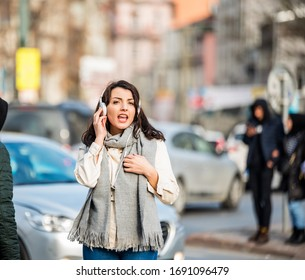 Beautiful young girl traveler in trendy casual wear listens music and sings while walking in crowd street