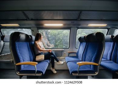 Beautiful young girl is traveling on a train. Trip. Transport.