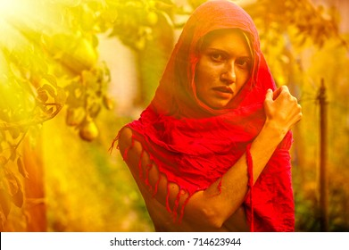Beautiful young girl trying on a red scarf. Autumn time for harvest. Orchard. The concept of harvesting.