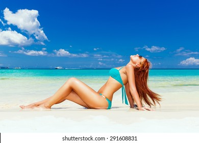 Beautiful young girl in turquoise bikini on a tropical beach. Blue sea in the background. Summer vacation concept.