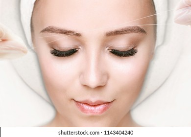Beautiful young girl tweezing her brows in a beauty salon. Beauty Concept. Cosmetologist plucks client eyebrows by thread. Eyebrow correction, threading. Permanent Makeup. Microblading brow. Close up.