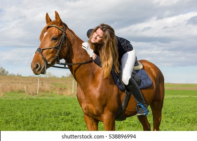 Beautiful young girl in uniform competition ride and stroke her brown horse : outdoors portrait on sunny day