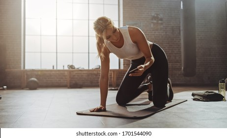 Beautiful and Young Girl Uses Smartphone App to Setup Timer For Her Exercise On Fitness Mat. Athletic Woman Does Mountain Climber Workout in Stylish Hardcore Gym