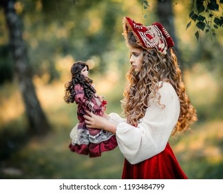 Beautiful young girl in  vintage dress and cute red hood outdoor. Art work of romantic girl with a doll. Pretty tenderness blonde model with huge blue eyes.