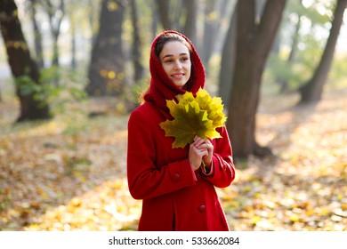 Beautiful young girl walking in autumn park.