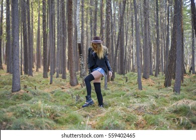Beautiful young girl walking in the autumn forest. The girl leaned on the tree. Magical fairy forest.
