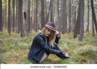 Beautiful young girl walking in the autumn forest. Girl sitting on the soft green grass.