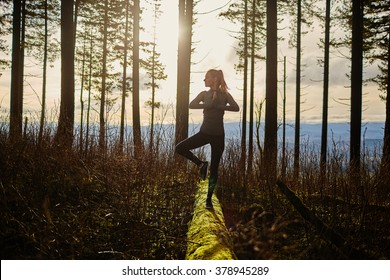 beautiful young girl walking in forest standing on log in yoga tree pose