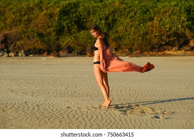 beautiful young girl walking on the beach in a pink dress and in a swimsuit