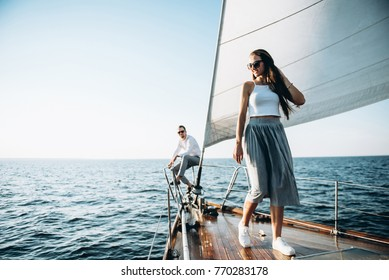 Beautiful young girl walks on a wooden yacht with sails. She swims with her handsome guy on the sea