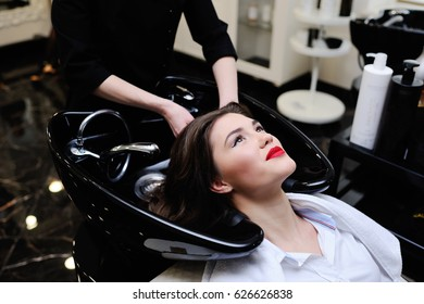 Beautiful young girl washing her head in a beauty salon