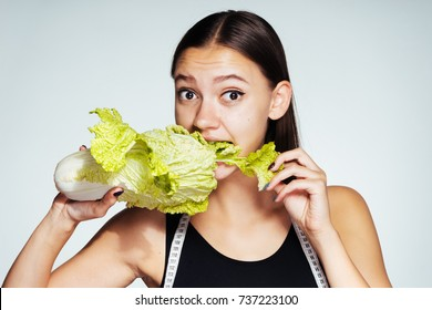 a beautiful young girl watches her weight, so she eats a healthy low-calorie Peking cabbage