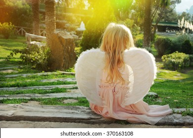 Beautiful young girl wearing angel wings