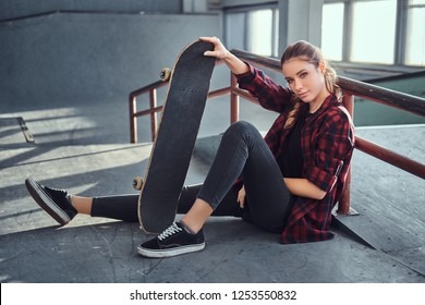 A beautiful young girl wearing a checkered shirt holding a skateboard while sitting next to a grind rail in skatepark indoors.