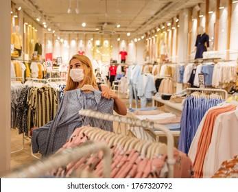 Schönes junges Mädchen mit Einweg-Gesichtsmaske wählt Kleidung im Kleiderladen.Leben mit neuen Normalzustand während covid19 Ausbruch.