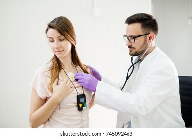 Beautiful young girl wearing Holter monitor device while doctor checking her health condition.