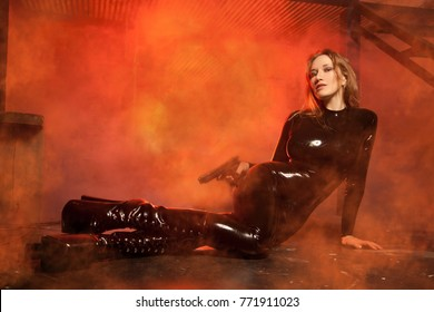 Beautiful Young Girl Wearing Latex Rubber Black Catsuit Posing with Gun in the Red Smoke