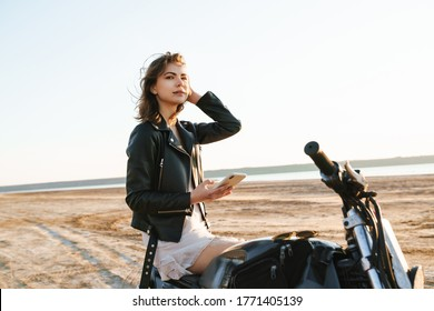 Beautiful young girl wearing leather jacket sitting on a motorbike at the sunny beach, using mobile phone