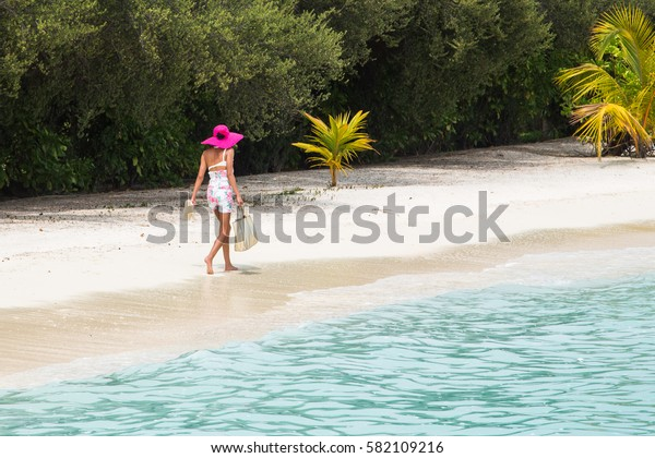 beautiful young girl wearing a pink hat walking along a beautiful beach with white sand and gorgeous turquoise water