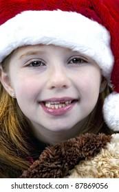 Beautiful young girl wearing Santa hat and smiling