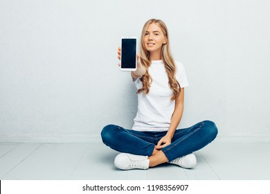 A beautiful young girl wearing a white t-shirt is sitting on the floor with her legs crossed showing a blank mobile phone screen on a grey background