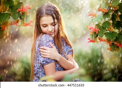 Beautiful young girl with wet hair enjoying the rain and looking down. Pretty woman in summer garden of viburnum hugging yourself..Happy rainy day.Colorful photo in warm colors.Leaves with rain drops.